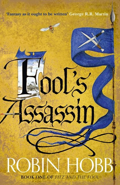 Fool's Assassin golden cover with gothic title, the first letter is illuminated, a flag to the right of the page
